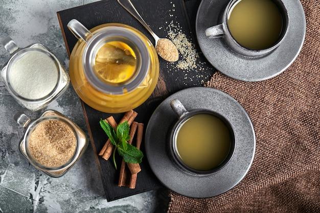 Teiera in vetro trasparente con tè chitrus e tazze, servizio da tè su un tavolo di legno