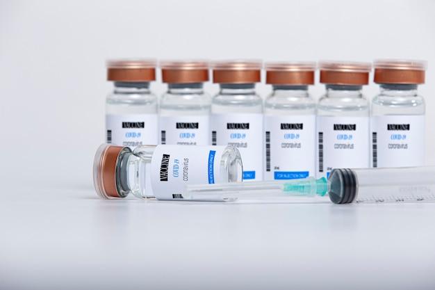 Flaconcini di vetro trasparente con vaccino covid-19 e siringa