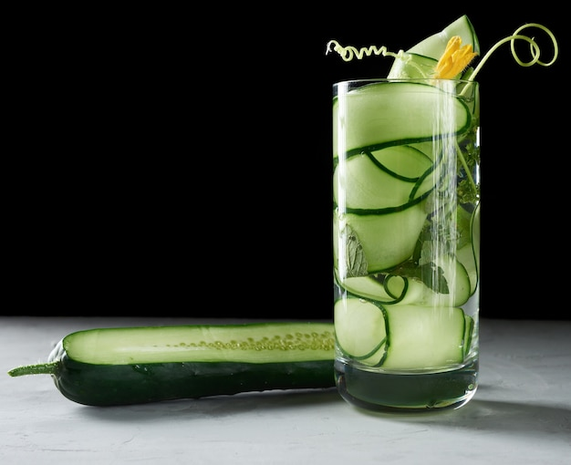 Vetro trasparente con pezzi di cetriolo, foglie di menta e acqua minerale, stile di vita sano, disintossicazione