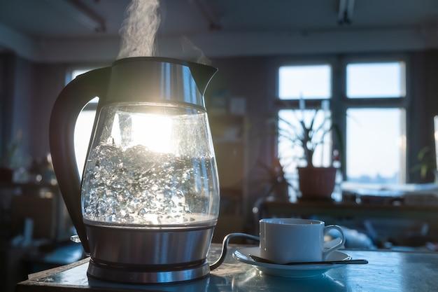 Un bollitore d'acqua trasparente bolle sullo sfondo del tramonto che splende attraverso la finestra