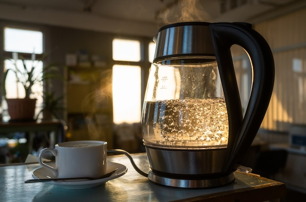 Un bollitore d'acqua trasparente ribolle contro la luce del tramonto che splende attraverso la finestra