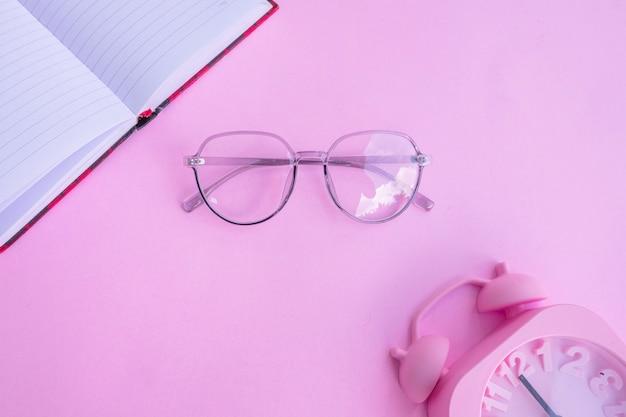 Occhiali rosa trasparenti su uno sfondo di carta rosa pastello con accessori pink book e alarm clock