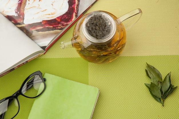 Teiera trasparente con tè verde con libro e bicchieri su una tovaglia verde
