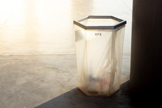 Pattumiera trasparente sul pavimento per copiare il testo dello spazio