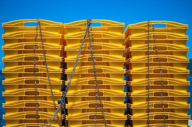 Contenitori di plastica di trasporto, mucchio di scatole gialle sul cielo blu