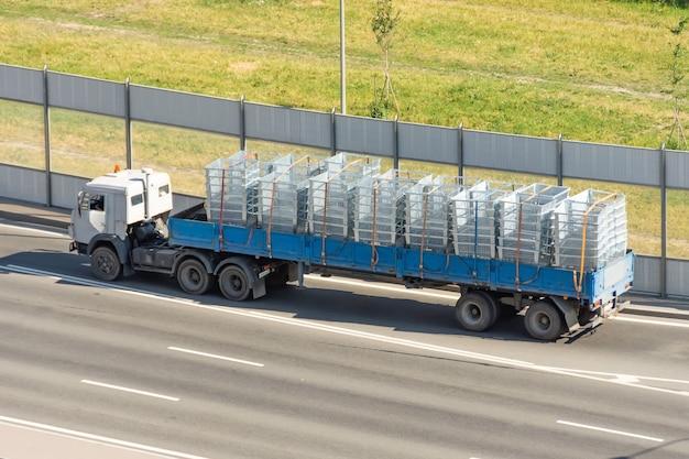 Trasporto e consegna di merci in un camion rimorchio aperto sull'autostrada, scatole di spedizione, carico con griglia metallica.