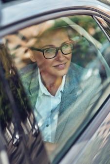 Trasporto e concetto di veicolo, bella e felice donna d'affari di mezza età che indossa occhiali da vista guardando fuori dal finestrino di una macchina e sorridente, seduto sul sedile posteriore in taxi, viaggio d'affari