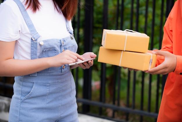 Il trasportatore vestito con l'uniforme arancione consegna i pacchi