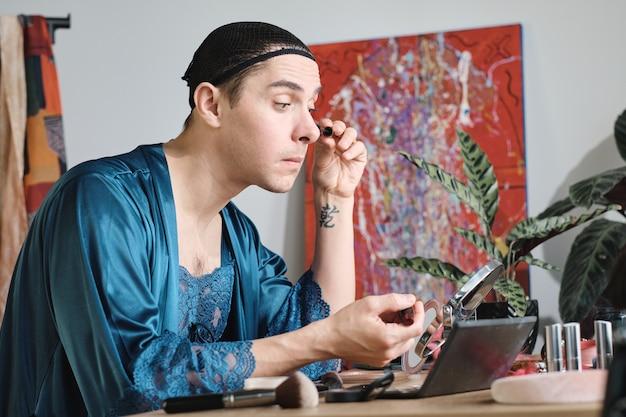 Transessuale in abito femminile seduto al tavolo davanti allo specchio e truccandosi sul viso