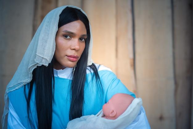 Vergine maria transessuale di fronte alla telecamera mentre tiene in braccio gesù bambino con tenerezza in una betlemme