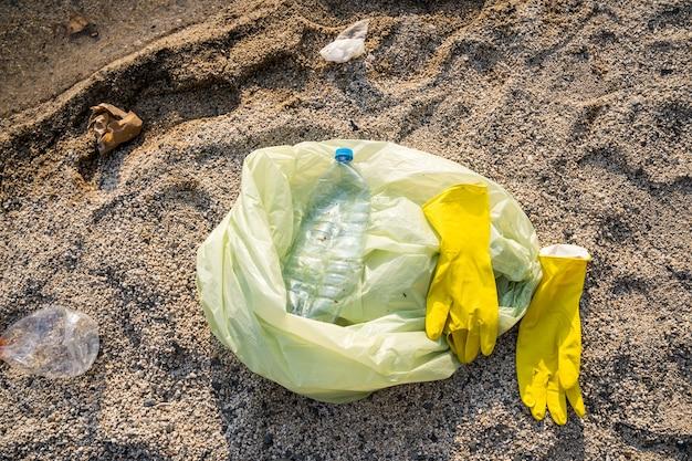 Il sacco della spazzatura e i guanti giacciono sulla sabbia. pulizia e concetto di protezione dell'ambiente.