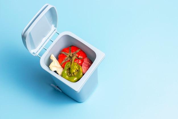 Pattumiera con spreco alimentare dentro sulla vista superiore del fondo blu, concetto di separazione dell'immondizia
