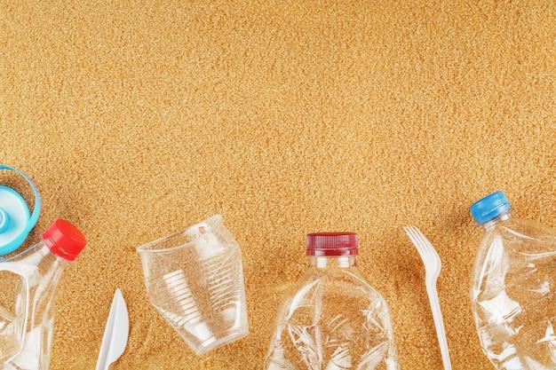 Cestino da bottiglie di plastica su una spiaggia sabbiosa con spazio libero
