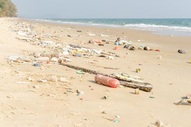 Cestino sulla spiaggia tropicale. problema ambientale di inquinamento da plastica. bottiglie di plastica e altri rifiuti lavati sulla spiaggia.