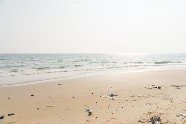 Cestino sulla spiaggia tropicale. problema ambientale di inquinamento di plastica. bottiglie di plastica e altri rifiuti lavati sulla spiaggia.