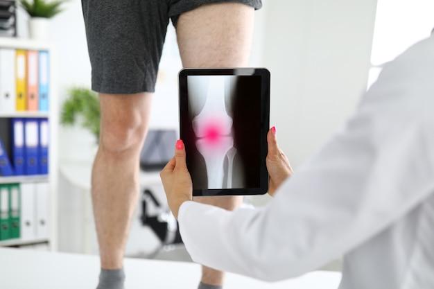 Il traumatologo sta tenendo la compressa vicino alla gamba dolorante dei pazienti nel primo piano della clinica