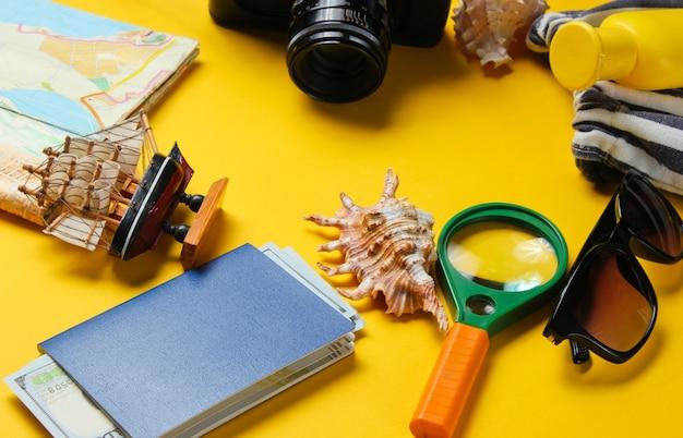 Accessori da viaggio e fotocamera retrò su sfondo giallo. sfondo spiaggia estiva. concetto di vacanza