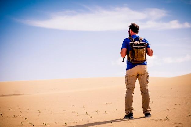 Concetto di viaggio e avventura con uomo in piedi con zaino e dune del deserto di sabbia con cielo blu