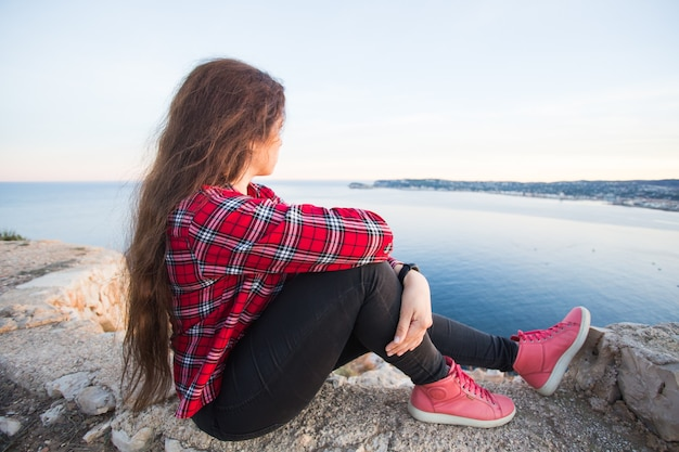 Concetto di viaggio, avventure e solitudine - una ragazza si siede sul bordo della scogliera e guarda il mare