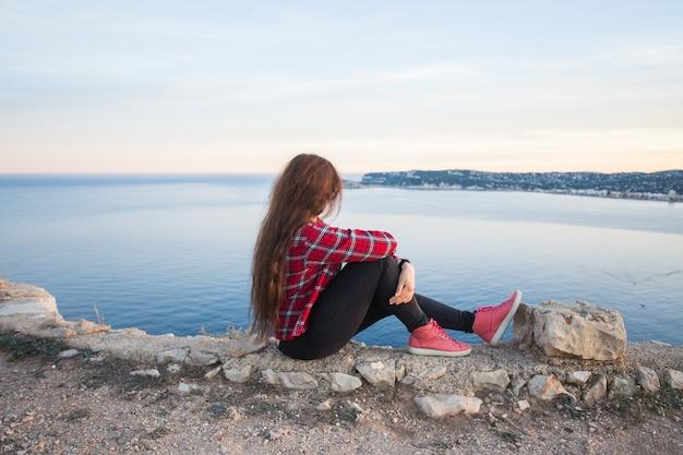 Avventure di viaggio e concetto di solitudine una ragazza si siede sul bordo della scogliera e guarda il mare