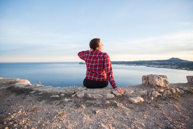 Viaggi, avventure e concetto di natura - turiste sedute da sole sulla montagna