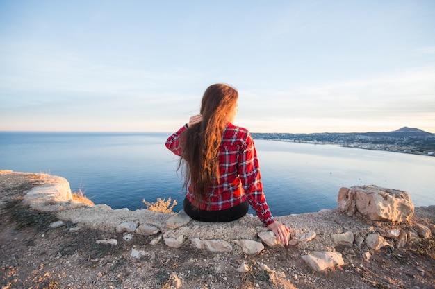 Avventure di viaggio e turisti femminili di concetto della natura che si siedono da solo sulla montagna