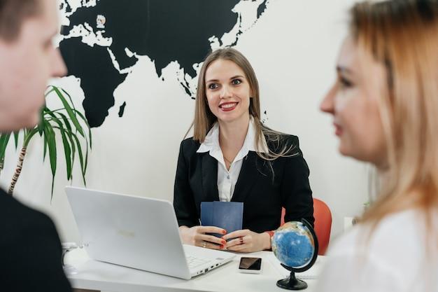 Agente di viaggio che lavora con il cliente nell'ufficio moderno e leggero dell'agenzia di viaggi