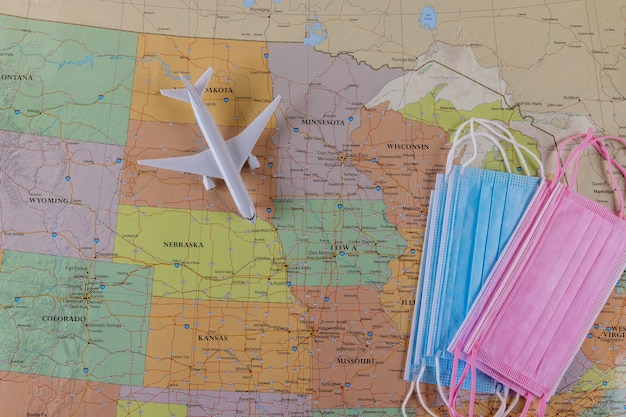 Viaggia in vacanza aerea durante la quarantena del coronavirus covid-19 con modello di aeroplano, maschera facciale sulla mappa degli stati uniti che mostra
