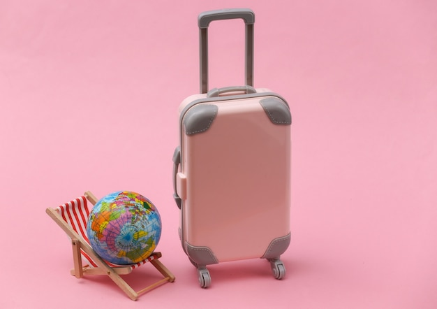 Concetto di viaggio o viaggio in spiaggia. mini valigia da viaggio e sedia dack con globo su sfondo rosa. stile minimal