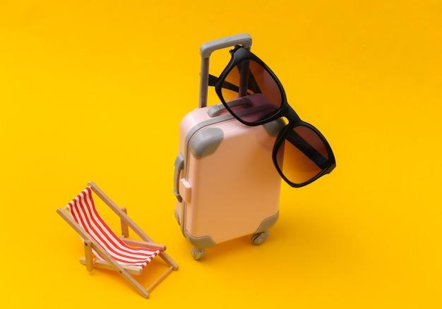 Concetto di viaggio o viaggio in spiaggia. mini valigia da viaggio con sedia a sdraio, occhiali da sole su sfondo giallo. stile minimal