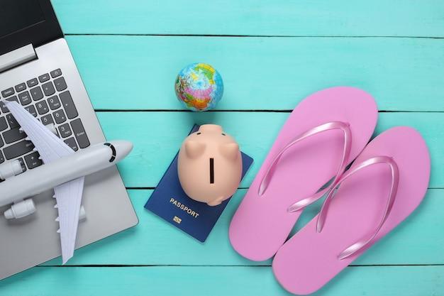 Viaggio o vacanza al mare laici piatta. viaggio, accessori da spiaggia, laptop su una superficie di legno blu. vista dall'alto