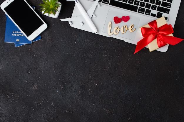 Concetto di prenotazione del viaggio. smartphone, modello di aeroplano, laptop, passaporti e confezione regalo su sfondo scuro.