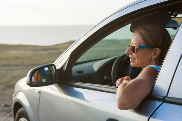 Viaggiare in macchina. la ragazza felice con gli occhiali guarda fuori dall'auto