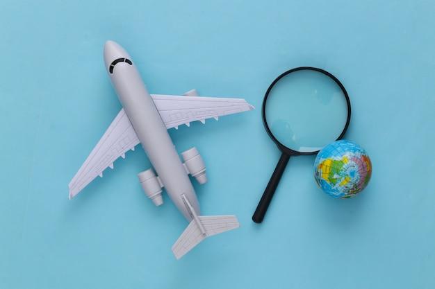 Concetto di viaggio. aereo, lente d'ingrandimento con un globo su un blu