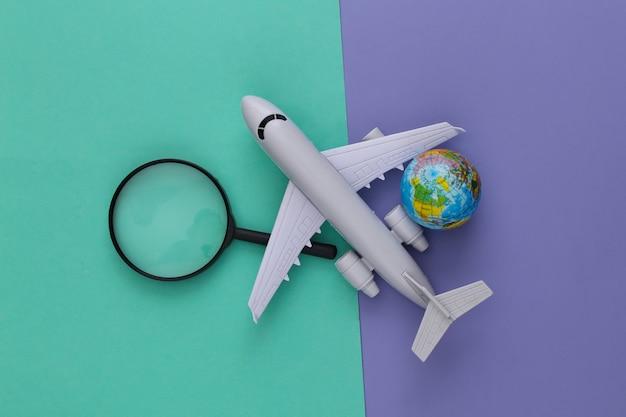 Concetto di viaggio. aereo, lente d'ingrandimento con un globo su viola blu