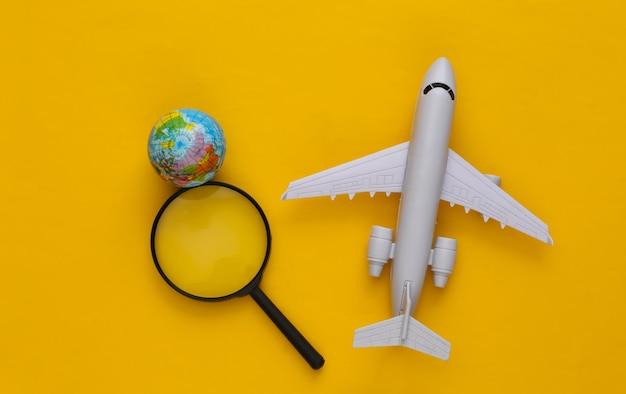 Concetto di viaggio. aereo, lente d'ingrandimento con un globo su giallo