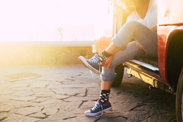 Concetto di viaggio per una vacanza alternativa per persone - donna con bei calzini fuori dal vecchio furgone vintage con la luce del sole al tramonto - signora che mette scarpe da ginnastica