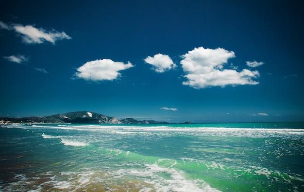 Concetto di viaggio - spiaggia con nuvole e cielo blu