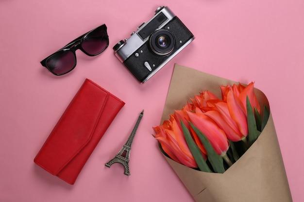 Concetto di viaggio. bouquet di tulipani rossi, macchina fotografica, statuetta della torre eiffel, occhiali da sole sul rosa