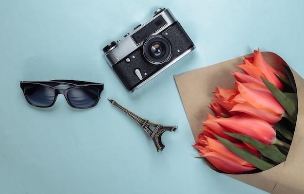 Concetto di viaggio. mazzo di tulipani, macchina fotografica, statuetta della torre eiffel, occhiali da sole sul blu