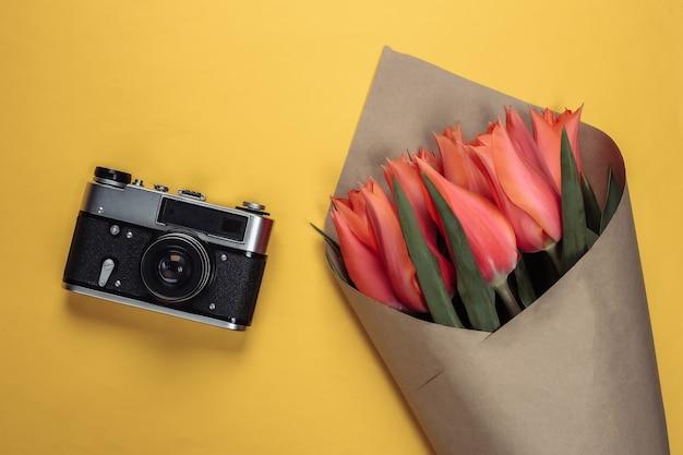 Concetto di viaggio. mazzo di tulipani e macchina fotografica su un giallo