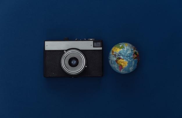 Concetto di viaggio. fotocamera e globo su sfondo blu classico. colore 2020. vista dall'alto.