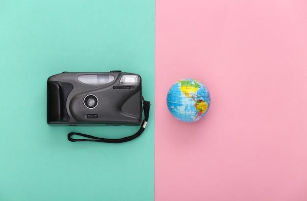 Concetto di viaggio. fotocamera con un globo su sfondo blu-rosa. vista dall'alto