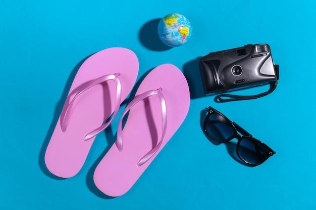 Concetto di viaggio. fotocamera con un globo, occhiali da sole, infradito su sfondo blu con ombra. vista dall'alto