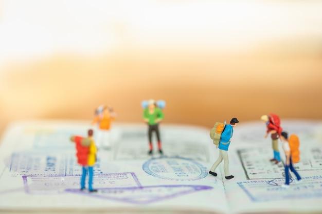 Concetto di viaggio. chiuda su del gruppo di figura miniatura del viaggiatore con lo zaino che cammina e che sta sul passaporto con l'immigrazione timbrato e lo spazio della copia.