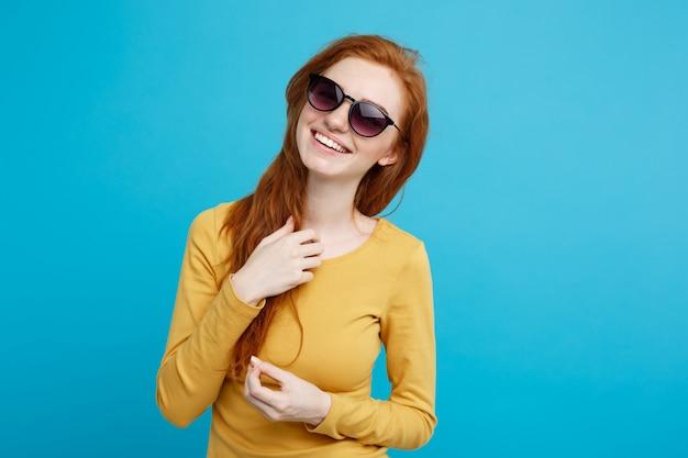Concetto di viaggio - close up ritratto di giovane bella ragazza attraente di zenzero rosso capelli con sorridente sunglass sorridente. sfondo blu pastello. copia spazio.