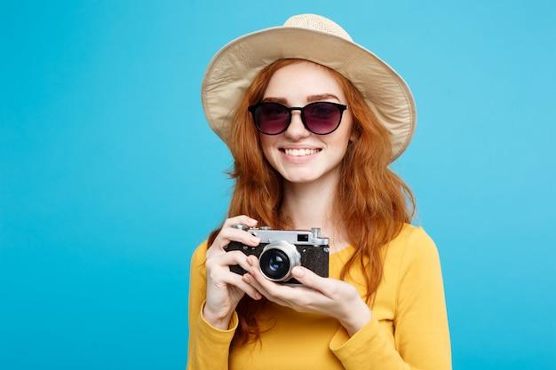 Concetto di viaggio - close up ritratto giovane bella ragazza attraente redhair con cappello alla moda, occhiali da sole e macchina fotografica vintage che sorride alla macchina fotografica. muro blu pastello. copia spazio.