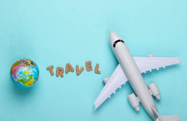 Concetto di viaggio. statuetta di un aereo passeggeri, globo blu