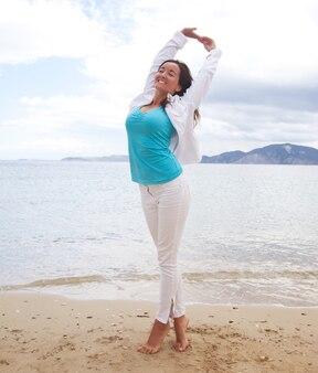 Concetto di viaggio - ragazza felice che salta sulla spiaggia, vacanze estive.