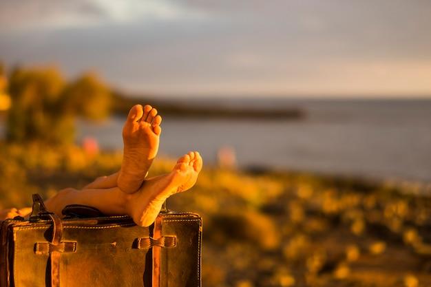 Immagine del concetto di viaggio. spiaggia e oceano in sfocato di piedi nudi femminili su vecchi bagagli vintage. riposarsi dopo un viaggio, vivere un viaggio e una vacanza meravigliosi